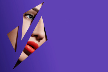 Plump bright red lips in violet paper frame. Young model face. Close up beauty photo. Geometry and minimalism. Creative fashion makeup Wall mural