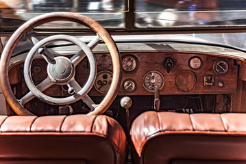 Cabin from inside a retro car. Wooden dashboard and steering wheel.
