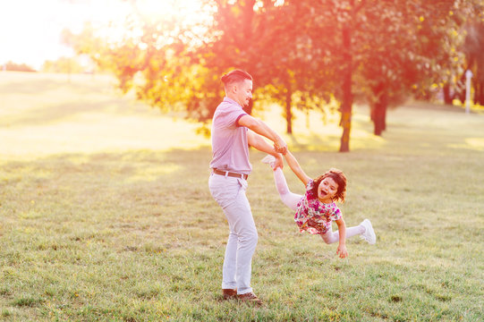 Handsome hipster father with mustache, hair style whirling his little daughter ootdoor on green field in park. Dad playing carousel with his cute child in multicolored dress. Parent with kid enjoying