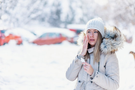 Portrait of a beautiful woman in snow with application of the protective cream in winter