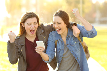 Excited friends watching phone content in a park