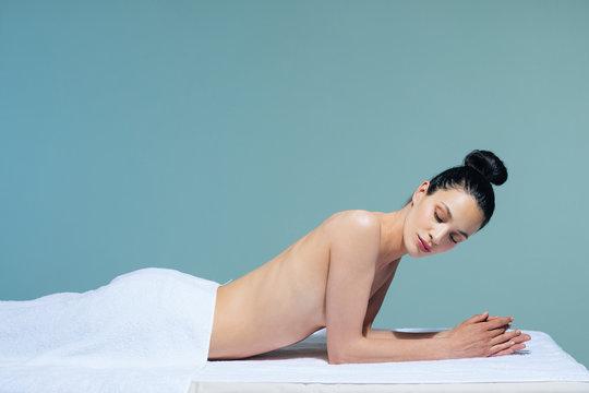 Beautiful Caucasian woman relaxing on massage table at wellness salon.