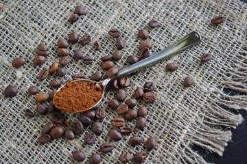 Coffee beans and coffee ground in a spoon on the burlap.