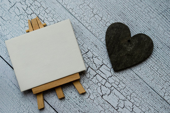 Small easel with a blank canvas over white and dark wooden heart. Old wooden background and big copy space for your sign and text. Landscape and flat rate