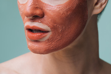 Unrecognisable cropped woman posing with orange lipstick and cosmetic face mask on her face.