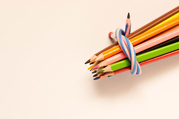 A set of colored pencils tied with a flexible pencil . Isolated on white background.
