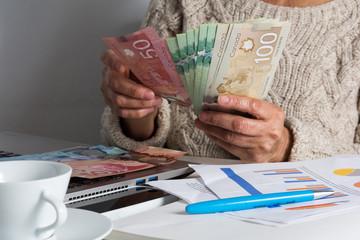 Money from Canada: Canadian Dollars. Senior person handling bill on desk.
