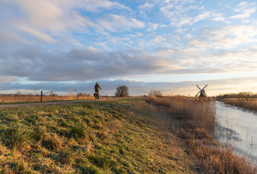 Woman cycling in the Dutch countryside near a traditional windmill. Groningen, the Netherlands.