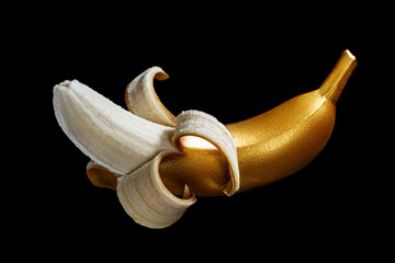 Golden banana on a black background. A modern creative concep with fruit