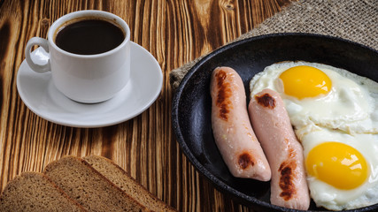 fried eggs with sausages and coffee. traditional modest breakfast