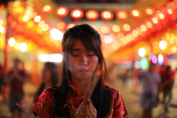 A woman lights incense while praying in a Chinese temple during the celebration of the Lunar New Year in Chinatown in Bangkok