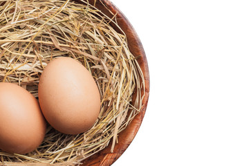Chicken eggs on rustic hay in wooden bowl isolated on white. Empty copy space healthy farm food background.