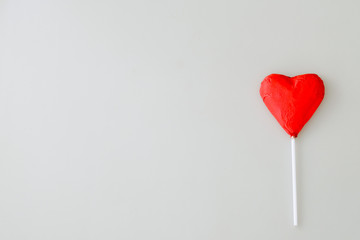Heart shaped chocolate candiy with red wrappings on a white background