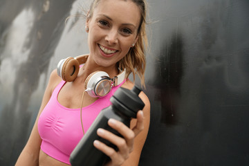 Happy fit woman in sportswear and workout accessories on black background