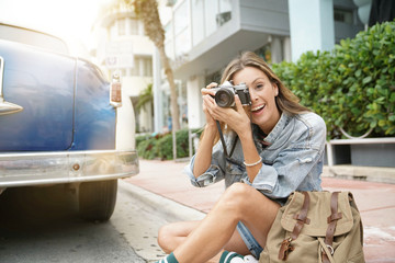 Attractive backpacker looking at vintage camera in city