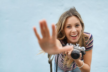 Dynamic photography student facing camera on blue background