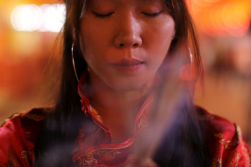 A woman lights incense while praying in a Chinese temple during the celebration of the Lunar New Year in the Chinatown in Bangkok