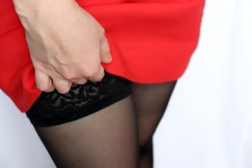Seductive woman in black lace stockings lifts the red dress. Sexy legs, concept of seduction, sex in the office, female fashion
