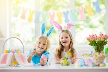Kids on Easter egg hunt. Children dye eggs.