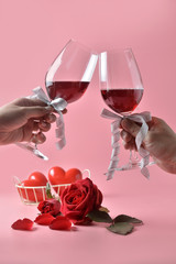 Clinking glasses of red wine in hands, with red rose on the bottom on pink background. Concept of Valentine's Day, pop art contemporary, celebrate.