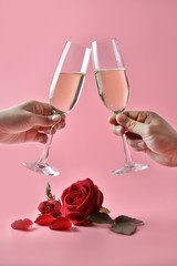 Clinking glasses of champagne in hands, with red rose on the bottom on pink background. Concept of Valentine's Day, pop art contemporary, celebrate.