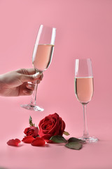 Champagne in glass on hand, with rose at the bottom on pink background. Concept of Valentine's Day, pop art contemporary, celebrate.