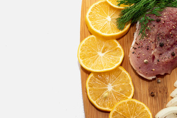Fresh raw pork meat with spices, lemon and onion on wooden cutting board