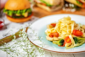 delicious Italian pasta with chicken, broccoli and cherry tomatoes on a white plate