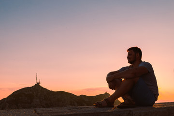 young adult man sitting on stone wall with beautiful view of sunset in mountains