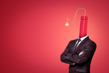 A waste-deep image of a businessman with a big dynamite stick with its wick burning instead of head on red background with a lot of copy space.