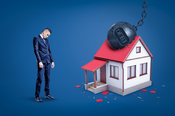 Sad businessman and metal chained ball with 'DEBT' sign breaking white private house.