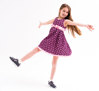 Cute girl in violet short dress, happy spinning and turning around, dancing