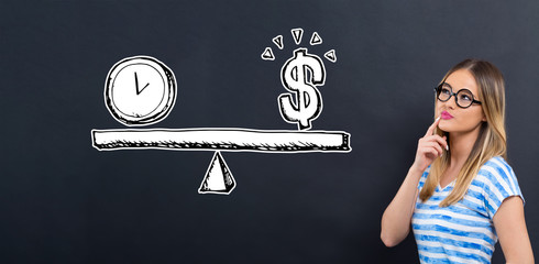 Time and money on the scale with young woman in front of a blackboard