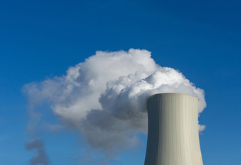 smoke from chimney or steam of power plant cooling tower on background of blue sky - fossil energy sources