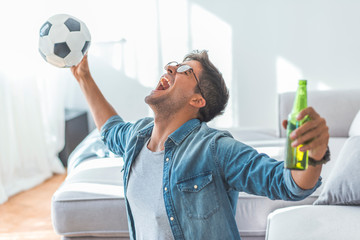 Excited mature man cheering while watching soccer match on sofa at home