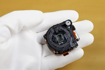 A technician controls the quality of a modern lens  for a photo camera