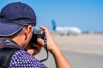 Man taking photos of huge airplane on the airport runway area