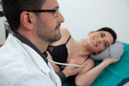 doctor controling his female patient using an ecography