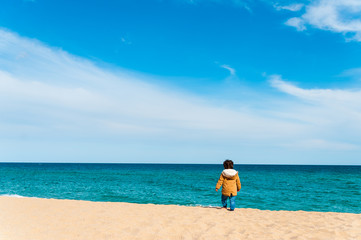lonely baby boy walking alone on sand beach during sunny day going away