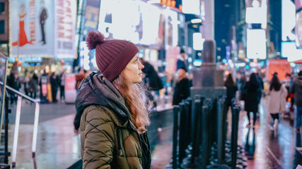 Young woman at New York Times by night