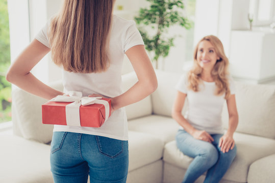 Close up back behind rear view photo guess what I have two people mum and teen daughter holding hands arms behind back gift box surprise wear white t-shirts jeans in bright kitchen sit on cozy sofa
