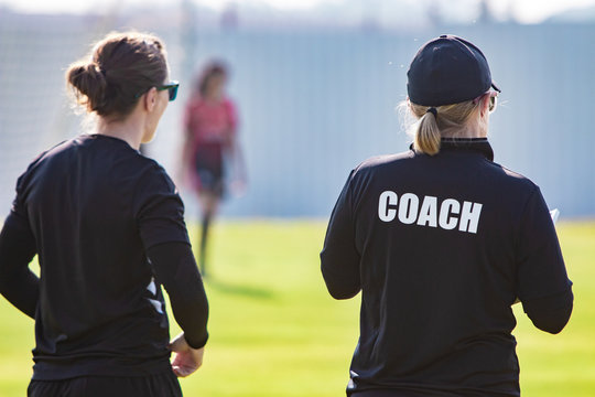 Back view of female sport coach and her assistant in black COACH shirt at an outdoor sport field