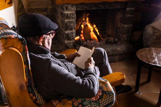 Relaxed senior man sitting in front of the fireplace