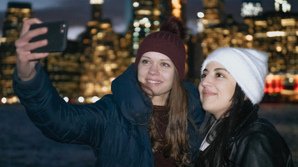 Two girls enjoy a wonderful night in New York in front of the Manhattan skyline