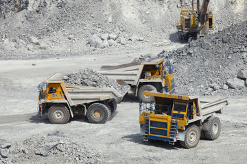 Large mining trucks in a quarry for limestone mining. Mining industry.