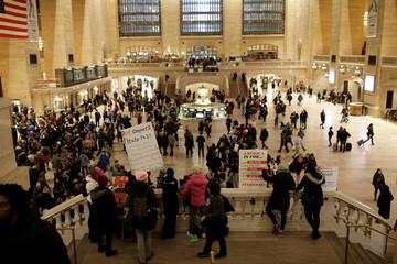 Demonstrators hold signage and flags in the upper concourse of Grand Central Station during Non-March for Disabled Women hosted by Rise and Resist with help from the Women's March NYC in Grand Central Station