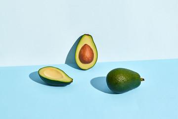 three half of Avocado fruits on blue background