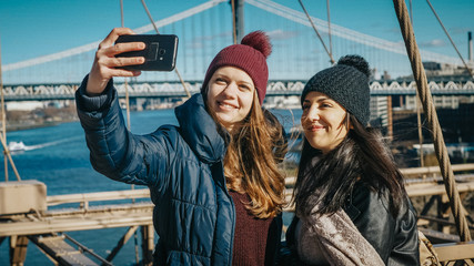 Two friends in New York walk over the famous Brooklyn Bridge
