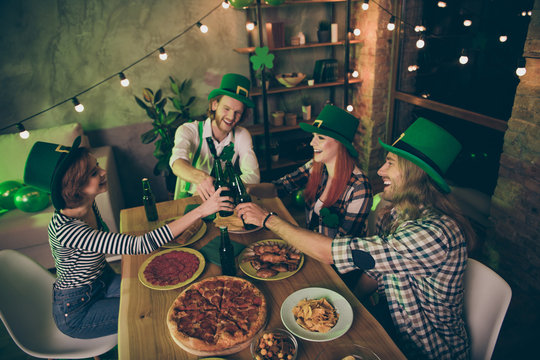 Close up photo gathered big table company four friends couples pairs love lovers tasty drinks green hats leaf pizza sausage chips irish culture home party leprechaun costumes