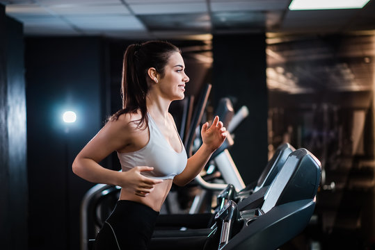 Young sports woman with ponytail working out in the gym, running on treadmill, side view.